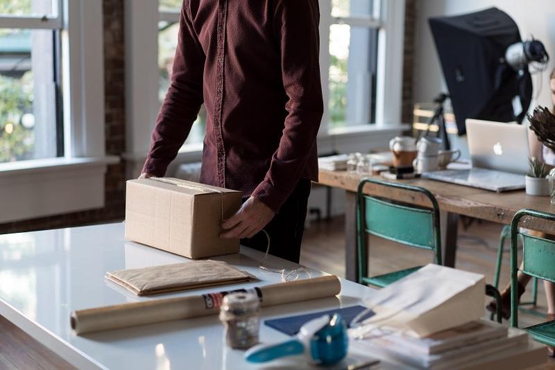 Mężczyzna składający opakowanie kartonowe w pracowni