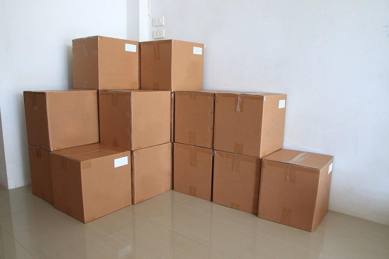 Stos pudełek kartonowych poukładanych przy ścianie